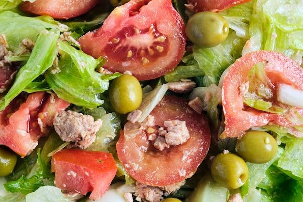 レタス、タマネギ、トマト、マグロの新鮮なサラダのクローズアップ