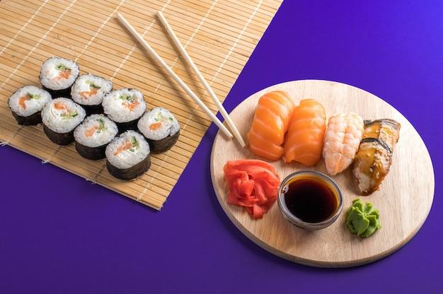 木の板と竹マットで提供される新鮮な寿司とロールのクローズアップ。