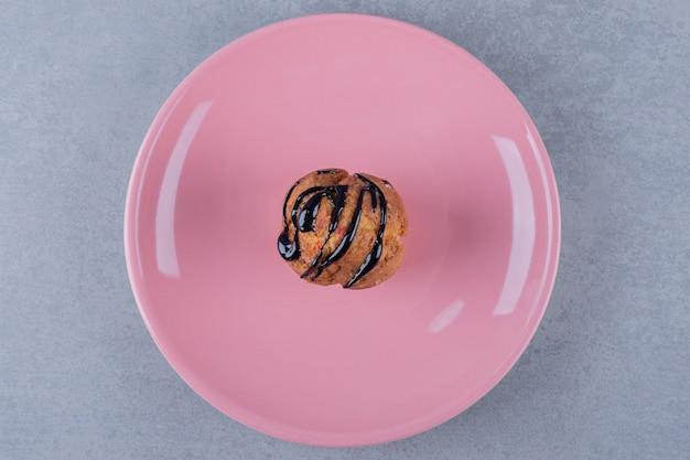 ピンクのプレートに新鮮な甘いマフィンのクローズアップ