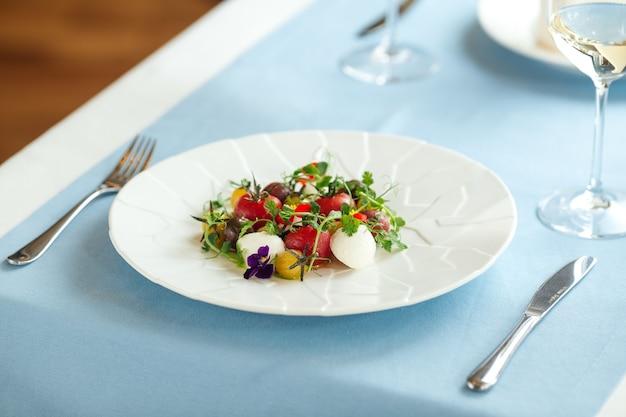 Крупный план салата из свежих помидоров с зеленью