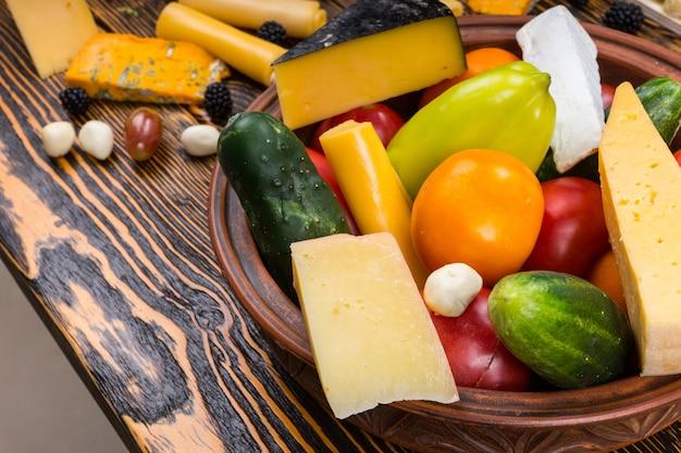 木目調の素朴な木製テーブルのボウルに新鮮な野菜の収穫とチーズのくさびのクローズアップ