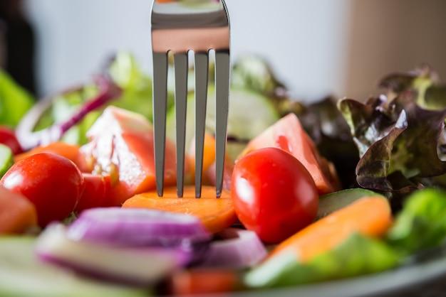 素朴な古い木製の背景とボウルで新鮮な野菜サラダのを閉じます。健康的な食べ物の概念。