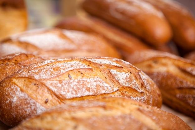 Крупный план свежего белого хлеба в булочках в пекарне, свежие буханки
