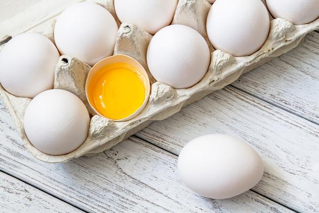 Конец-вверх свежих белых органических куриных яиц в бумажном подносе и яичного желтка на светлой деревянной предпосылке. вид сверху