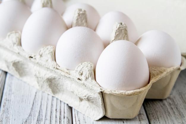紙トレイの新鮮な白い有機鶏の卵のクローズアップ