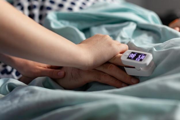 診察中に励ましを与える病室で、患者の手を握ってフレンドリーな医師の手のクローズアップ