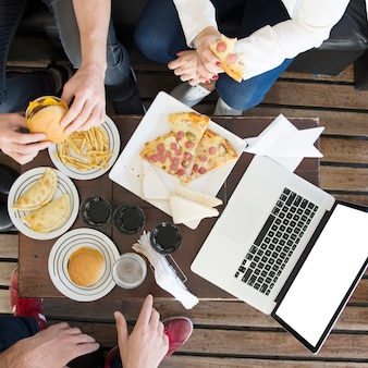Крупным планом друзей, едят закуски с напитками и ноутбук на столе