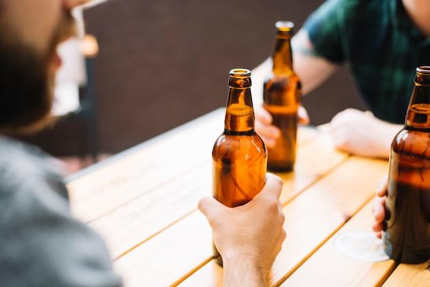 木製のテーブルにビール瓶を持っている友人のクローズアップ
