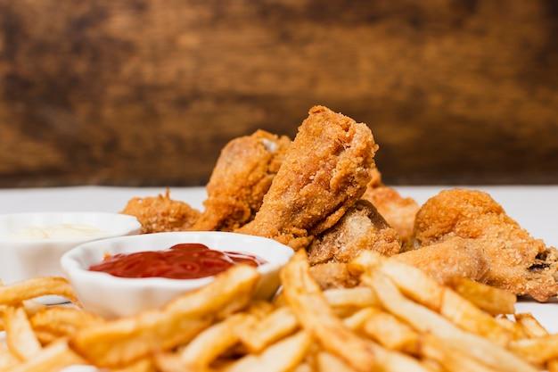Крупный план картофеля фри и жареной курицы
