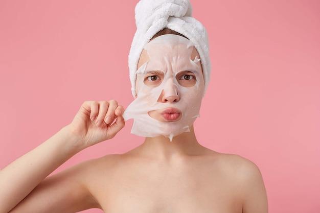 Крупным планом нахмуренная молодая женщина с полотенцем на голове после душа, пытается снять тканевую маску с лица, стоит.