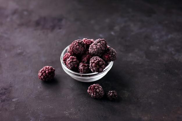 暗い背景の上の冷凍ブラックベリーのクローズアップ健康食品ビタミンスナックデザート