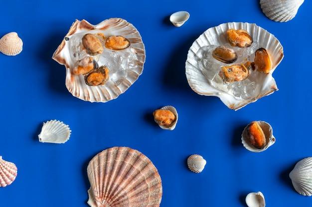 파란색 배경에 짓 눌린 얼음과 조개 껍질에 냉동 껍질을 벗긴 홍합 고기의 근접