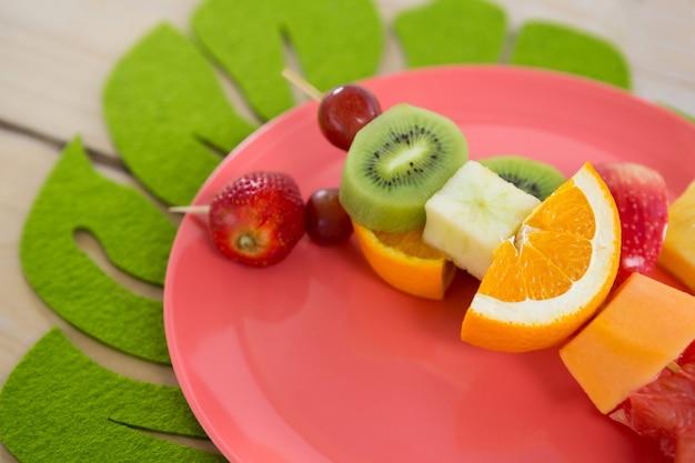 Крупный план фруктовых шашлыков в тарелке на деревянном столе