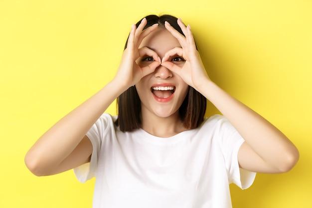 손 쌍안경을 통해보고 웃 고, 노란색에 대 한 t- 셔츠에 서있는 재미있는 아시아 여자의 닫습니다.