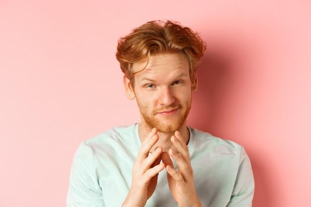 完璧な計画を立てる赤い髪の面白いひげを生やした男のクローズアップ、笑顔と尖塔の指、何かを計画し、ピンクの背景に対して悪意を持って立っています。