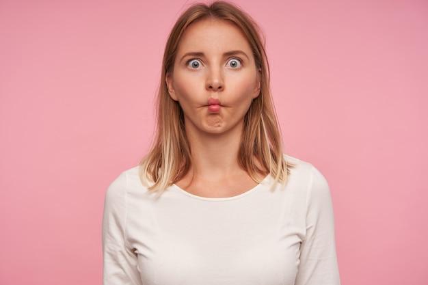 ピンクの背景の上に立って、目を大きく開いて唇を折りたたんでカメラを見て、カジュアルな髪型で顔を作る面白い青い目のブロンドの女性のクローズアップ