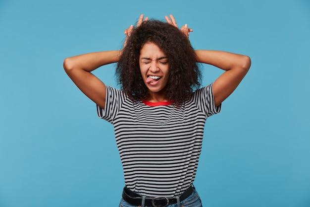 재미 있은 농담 아름다운 젊은 여자의 닫습니다, 행복을 느끼고, 손가락으로 그녀의 머리에 뿔을 만든다