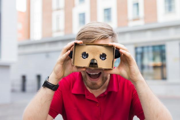 段ボールの仮想現実ゴーグルを屋外で使う変な男のクローズアップ