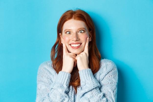 青い背景に立って、顔を作って、目を細めて頬を絞って、面白い赤毛の十代の少女のクローズアップ