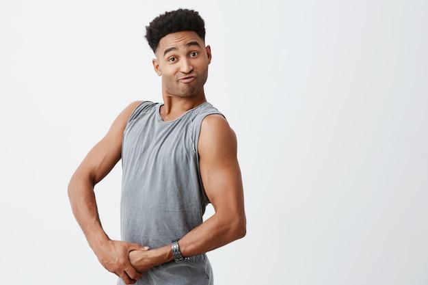 Закройте вверх смешного молодого афро спортсмена при вьющиеся темные волосы играя с мышцами, смотря в камере с смешным выражением стороны. здоровье и красота. копировать пространство