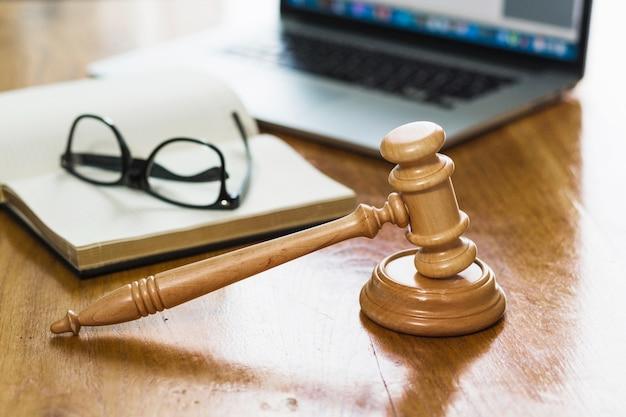 Крупный план молотка; книга; ноутбук и очки на деревянном столе