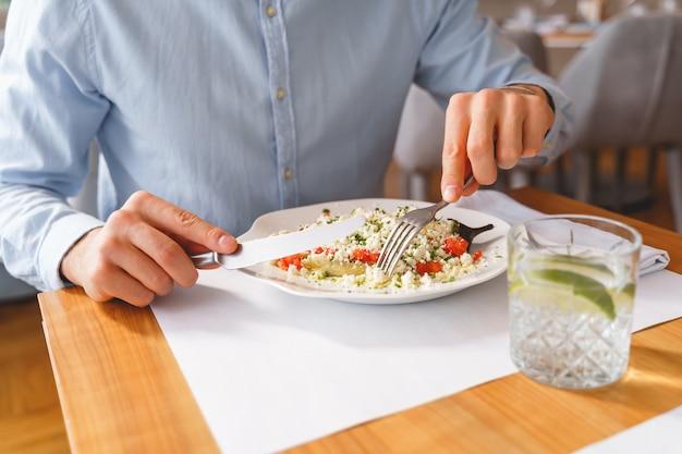 건강한 음식과 물 한 잔을 들고 식탁에 앉아 있는 동안 포크와 나이프를 들고 있는 신사의 클로즈업