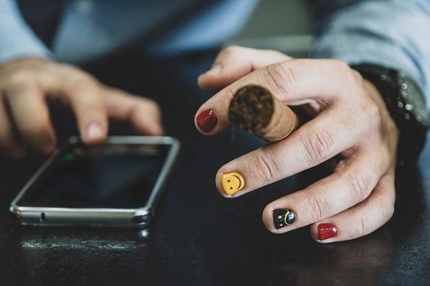 현대 스마트폰을 들고 시가를 피우는 신사의 클로즈업. 페인트 손톱을 가진 남자입니다. 남성 손톱의 디자인. 남자 매니큐어. 남자는 담배를 피우고 휴가에 스마트폰을 사용합니다. 여가 시간
