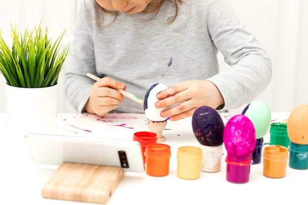 携帯電話を使用してイースターの卵を着色する女の子のクローズアップ