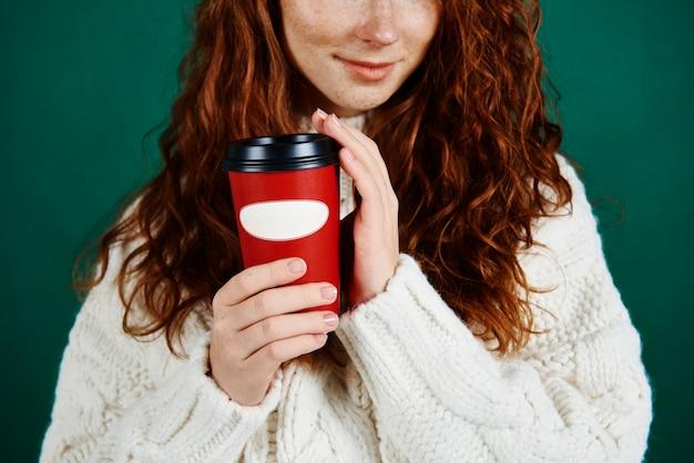 コーヒーの使い捨てマグカップを保持している女の子のクローズアップ