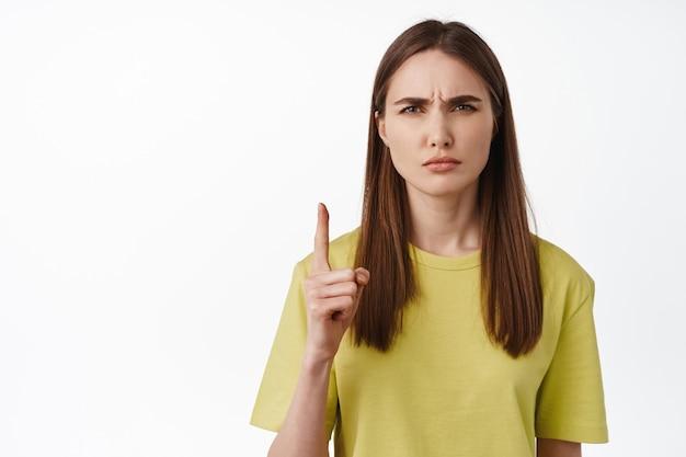 女の子のクローズアップは混乱した顔をします、それを取得しないでください、上向きに、眉をひそめ、目を細めて困惑し、smthを理解できず、白の上に立っています。