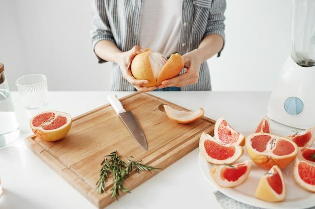 白い壁にグレープフルーツを剥離の女の子のクローズアップ。健康的なフィットネス栄養の概念。