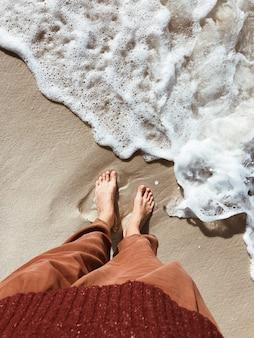 ビーチのそばの水の上を歩いている女の子の足のクローズアップ。濡れた砂に反射する海沿いの人。
