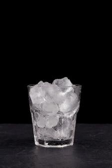 氷で満たされたガラスの透明なガラスのクローズアップ。飲み物やカクテルを作るための本物の角氷。黒の背景
