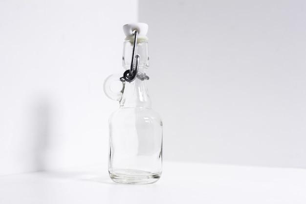 Крупный план стеклянной термо-бутылки на белом.