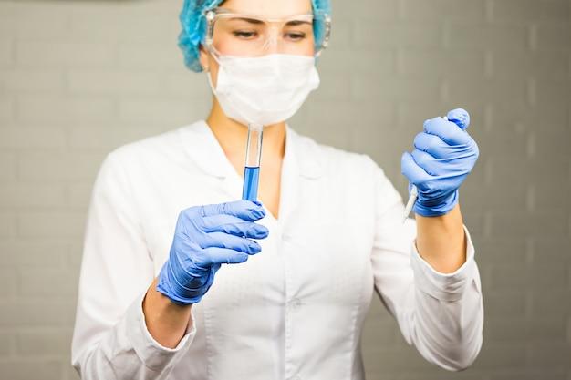 Крупный план стеклянной трубки с синей жидкостью в руке медсестры во время медицинского обследования