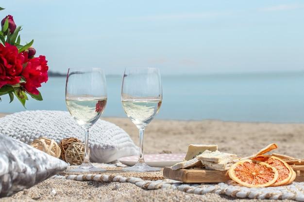 해변에서 샴페인과 스낵의 안경 닫습니다. 휴가 및 로맨스 개념.