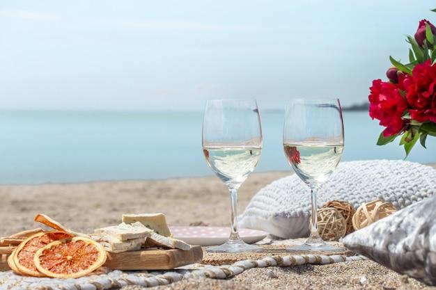 海岸のシャンパンと軽食のグラスのクローズアップ。休暇と恋愛の概念。