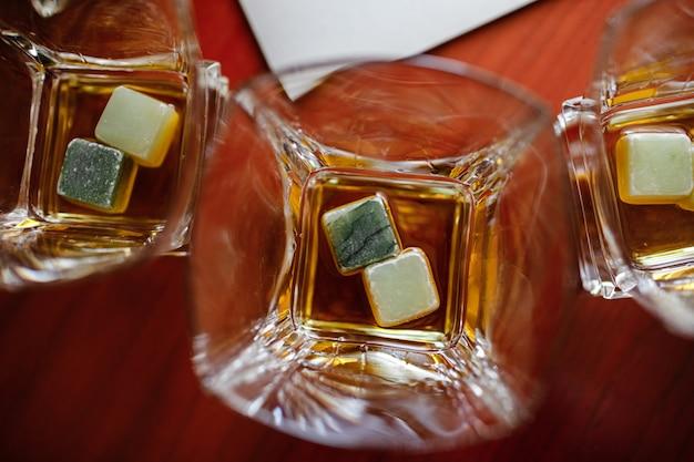 Крупным планом бокалов виски со специальным льдом на деревянном столе