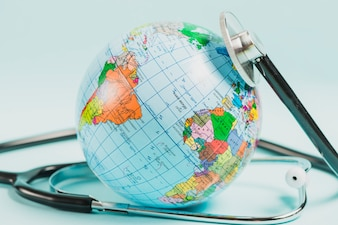 Close-up of globe with stethoscope against blue backdrop