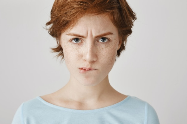 흰 벽에 포즈 우울한 빨간 머리 소녀의 근접 촬영