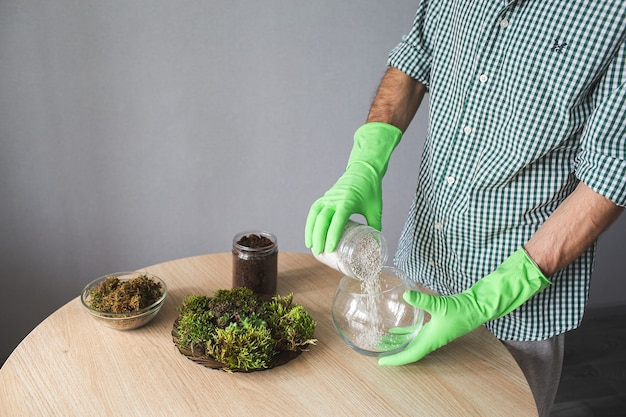 Крупный план рук в перчатках, наливающих перлит в вазу. подготовка к пересадке комнатных растений.