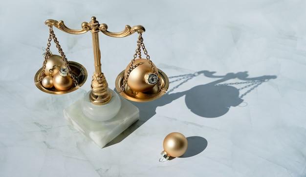 金色のクリスマスボールと金と大理石の装飾的なバランススケールのクローズアップ