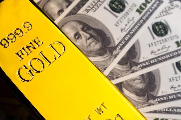 Закройте вверх золотого слитка и банкнот. финансовая концепция