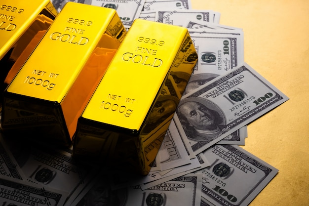 Закройте вверх золотых слитков и банкнот. финансовая концепция
