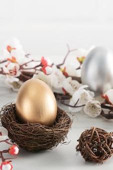 밝은 흰색 나무 테이블 배경에 흰 매 화 꽃과 둥지에 황금과 부활절 달걀 닫습니다.