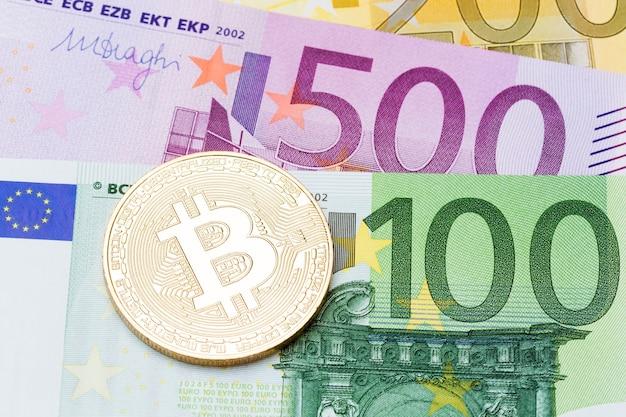 Закройте золотых биткойнов на фоне валюты евро. фотография высокого разрешения.