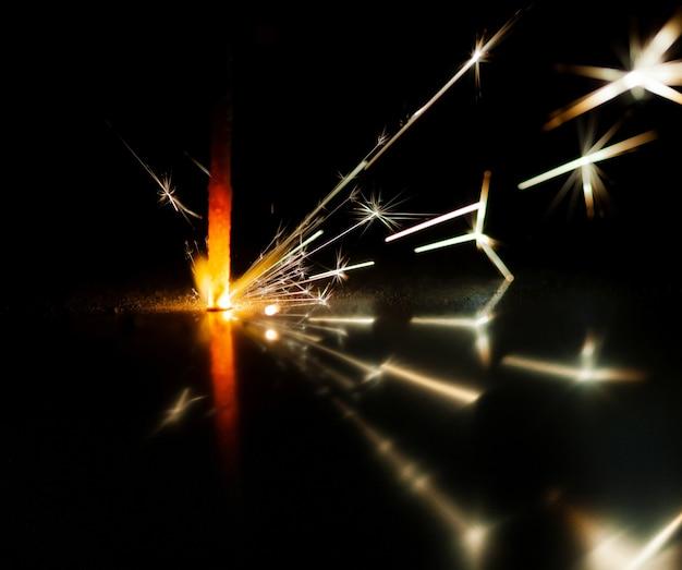 金色のぼやけた火花のクローズアップは、お祝いのキャンドルの光から暗闇の中で燃えます。花火のコンセプトと休日と新年あけましておめでとうございます。コピースペース