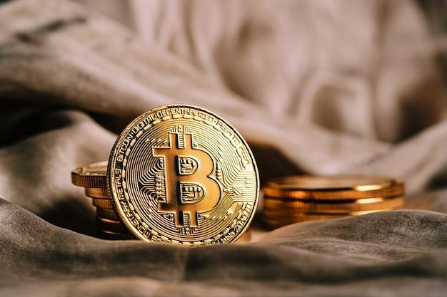 黄金の暗号通貨ビットコインと焦点の定まらない背景のクローズアップ
