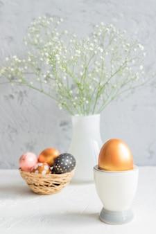 カスミソウと枝編み細工品バスケットの花束の背景に卵カップの黄金の卵のクローズアップ。居心地の良いイースター静物