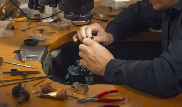 다이아몬드로 소중한 반지를 장식하는 금세공인의 클로즈업. 특별한 장비를 사용하는 전문 보석상. 금 보석 생산 개념